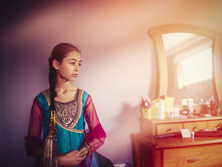 Mixed race girl wearing Indian dress in bedroom
