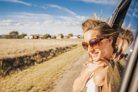 Hispanic woman leaning head out car window