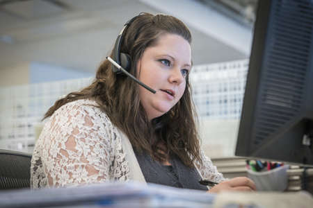Caucasian businesswoman talking on headset at office desk