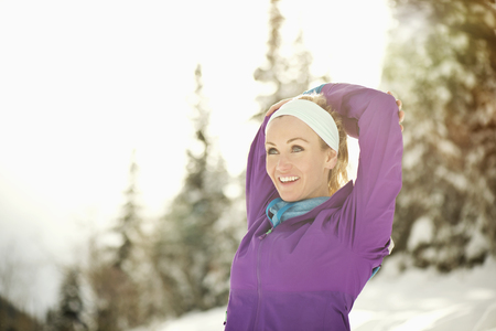 Caucasian woman stretching in snow