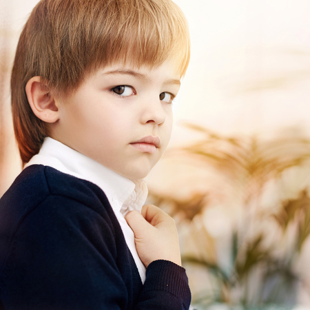 Close up of Caucasian boy wearing schoolboy uniform LANG_EVOIMAGES
