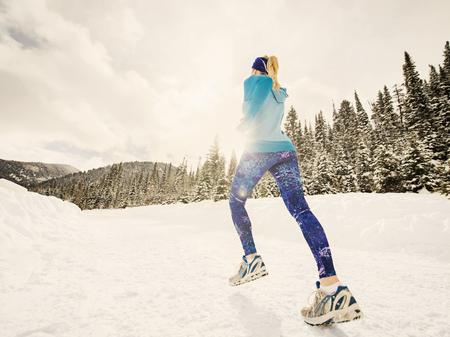 Caucasian woman running in snowy landscape