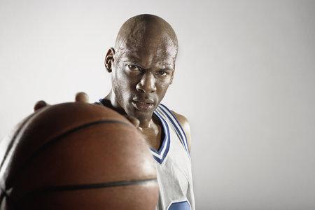 Sweating Hispanic basketball player holding basketball LANG_EVOIMAGES