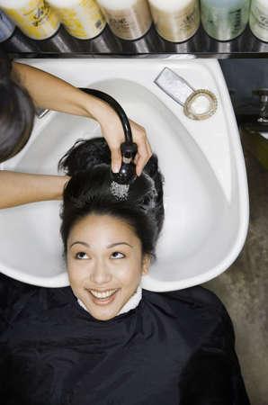 Pacific Islander woman having hair washed at salon LANG_EVOIMAGES