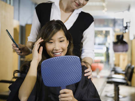 Asian woman looking at hair in salon LANG_EVOIMAGES