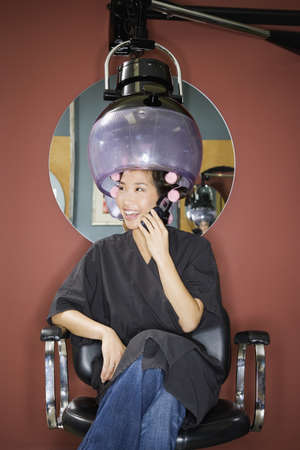 Asian woman under hair dryer in salon LANG_EVOIMAGES
