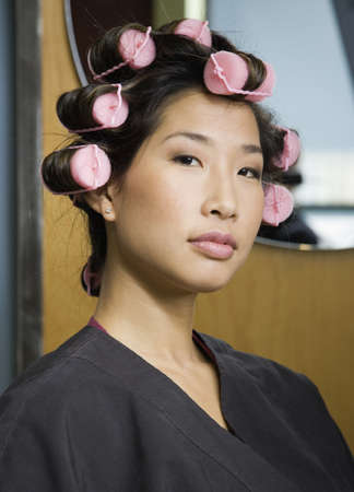Asian woman with curlers in hair