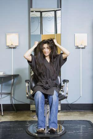Hispanic woman pulling on hair in salon LANG_EVOIMAGES