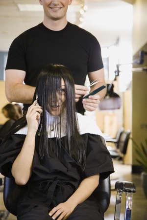 Male hair stylist cutting womans hair
