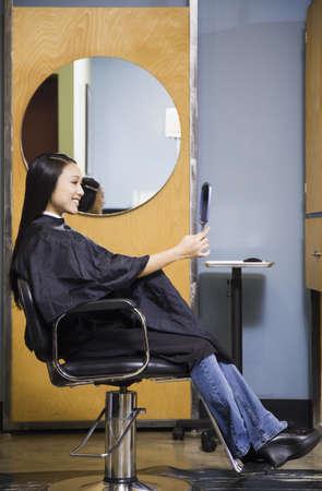 Pacific Islander woman looking at hair in salon