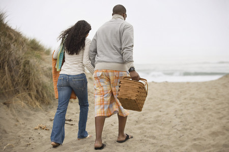 Couple walking on beach with picnic basket LANG_EVOIMAGES