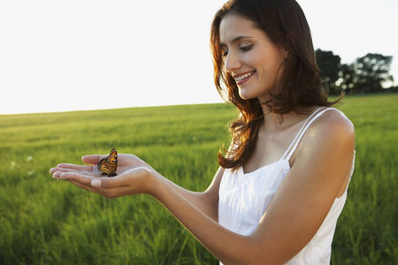 Woman holding butterfly in hands