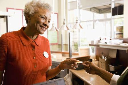 Senior African clerk taking customer's credit card LANG_EVOIMAGES