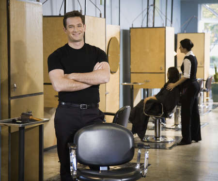 Male hair stylist in salon LANG_EVOIMAGES