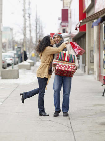 African couple kissing and carrying Christmas presents