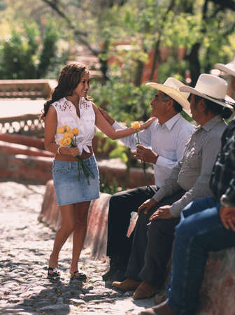 Hispanic woman giving flowers to her father LANG_EVOIMAGES