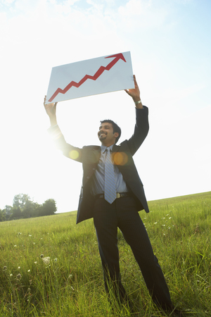 Indian businessman holding up arrow graph in field LANG_EVOIMAGES