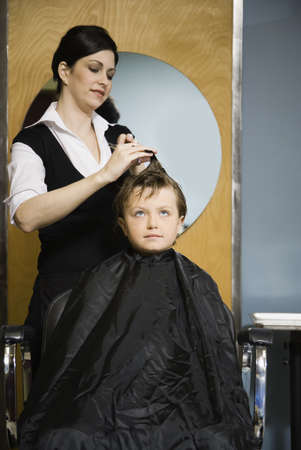 Female hair stylist cutting childs hair