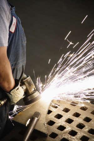 Man using sanding tool on metal