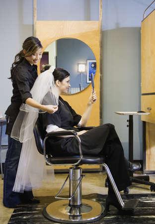 Bride looking at hair and veil at salon