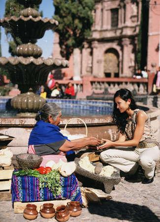 Hispanic woman buying tortilla from street vendor LANG_EVOIMAGES