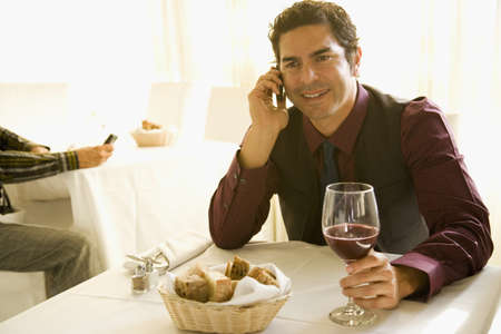 Hispanic man drinking wine and talking on cell phone in restaurant LANG_EVOIMAGES