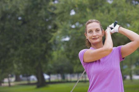 Mixed race woman swinging golf club