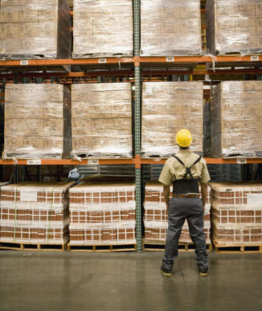 Male warehouse worker looking at stacks of boxes