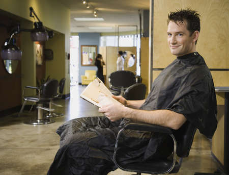 Man reading in hair salon chair LANG_EVOIMAGES