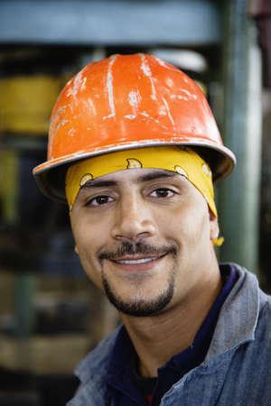 Close up of Hispanic man wearing hard hat LANG_EVOIMAGES