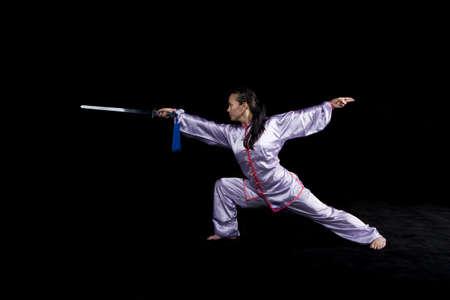 Pacific Islander woman practicing martial arts with sword