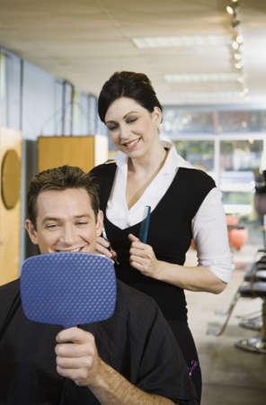 Man looking at hair in salon