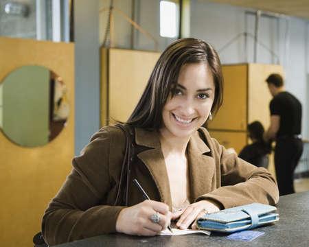 Hispanic woman writing check at salon