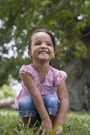 Grinning Hispanic preschool girl squatting in grass