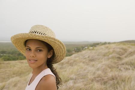Hispanic girl in straw hat in remote field