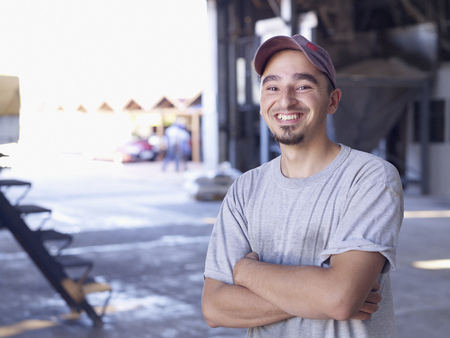 Hispanic worker smiling in factory LANG_EVOIMAGES