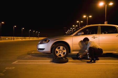 African businessman changing flat tire in parking lot