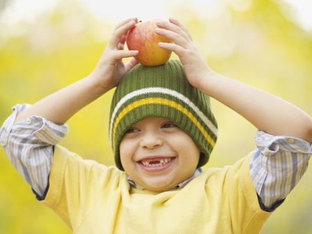 Toothless Hispanic boy balancing apple on head LANG_EVOIMAGES