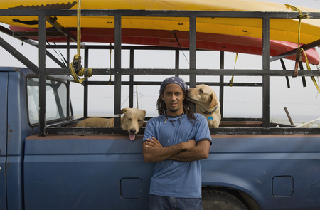 Hispanic man with dogs leaning against truck LANG_EVOIMAGES