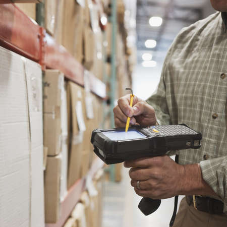 Hispanic man using tracking scanner in warehouse