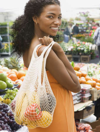 African woman carrying bag of fruits and vegetables LANG_EVOIMAGES