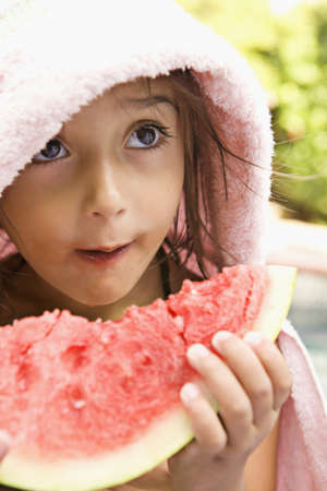 Mixed race girl enjoying slice of watermelon LANG_EVOIMAGES