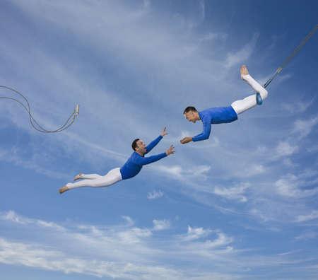Trapeze artist watching partner fall LANG_EVOIMAGES