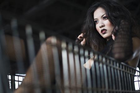 Asian woman sitting in shopping cart