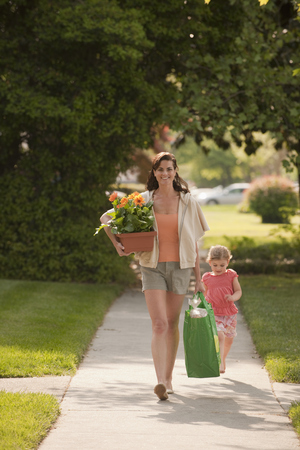 Caucasian mother and daughter returning with groceries LANG_EVOIMAGES