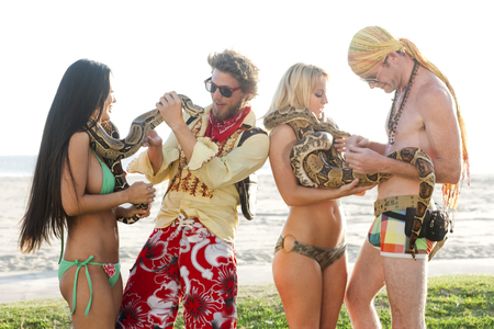 People looking at boa constrictors on beach LANG_EVOIMAGES