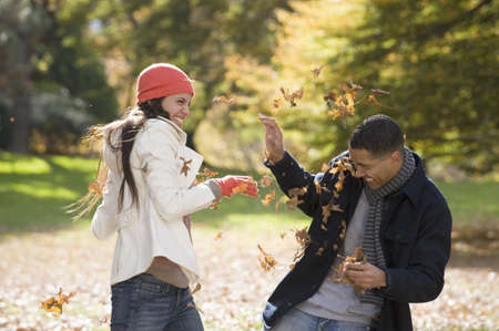 Couple playing in autumn leaves in park
