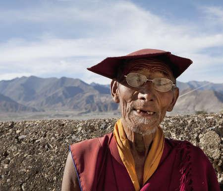 Elderly Tibetan monk in eyeglasses and hat LANG_EVOIMAGES