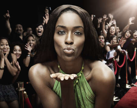 Mixed race celebrity blowing kisses at red carpet event LANG_EVOIMAGES
