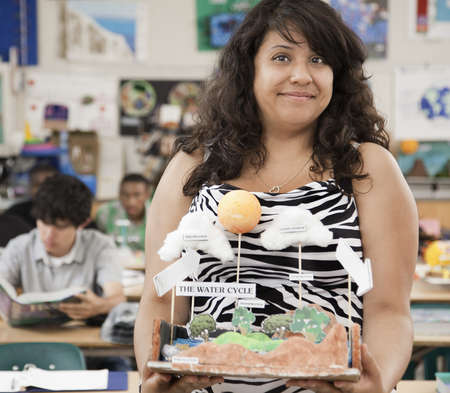 High school student holding science model of the water cycle